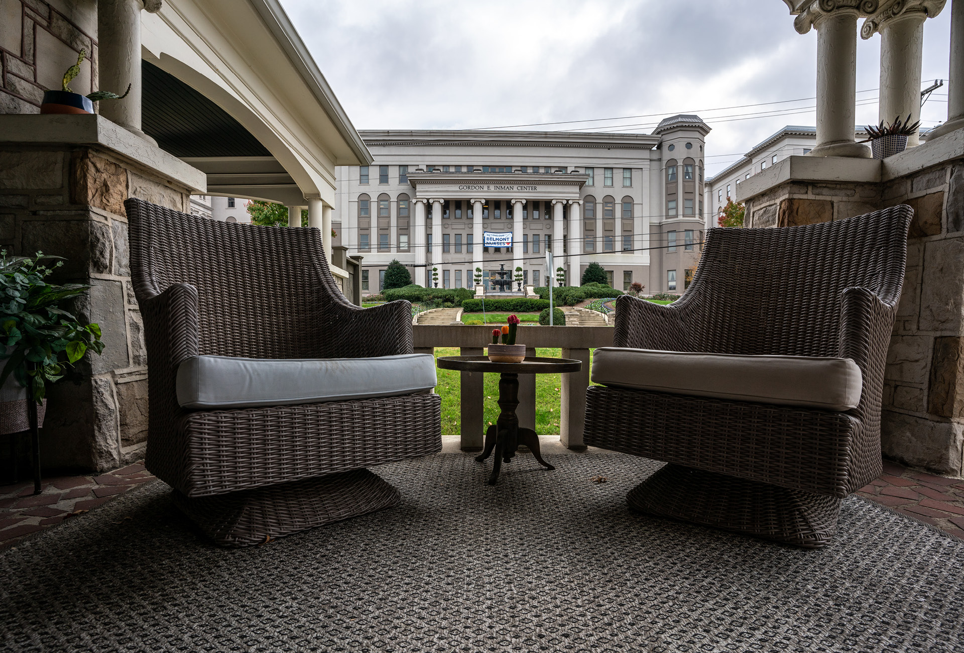 A cozy front porch with two chairs and Belmont University in the background