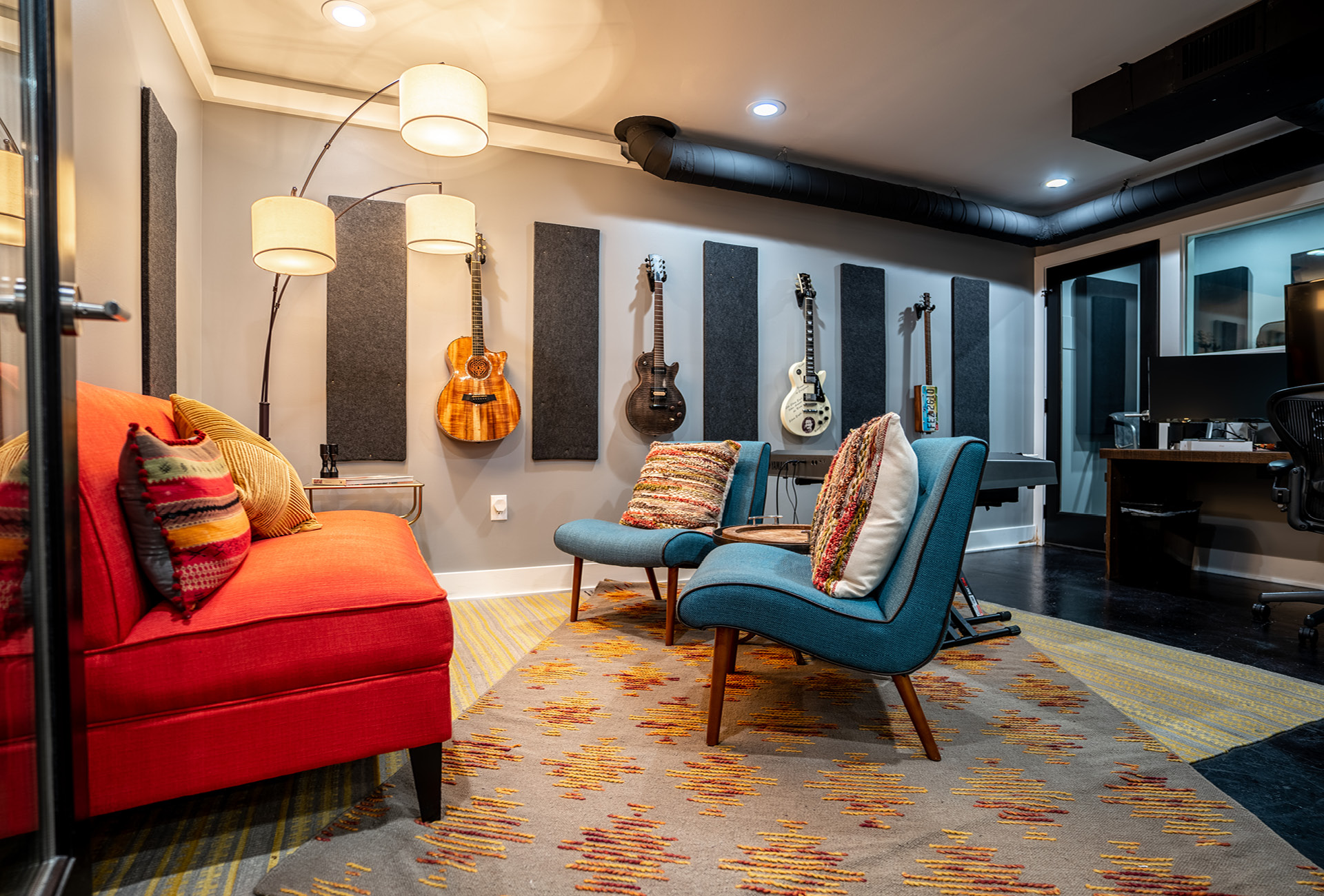 A recording room with keyboard, guitars, and plenty of seating