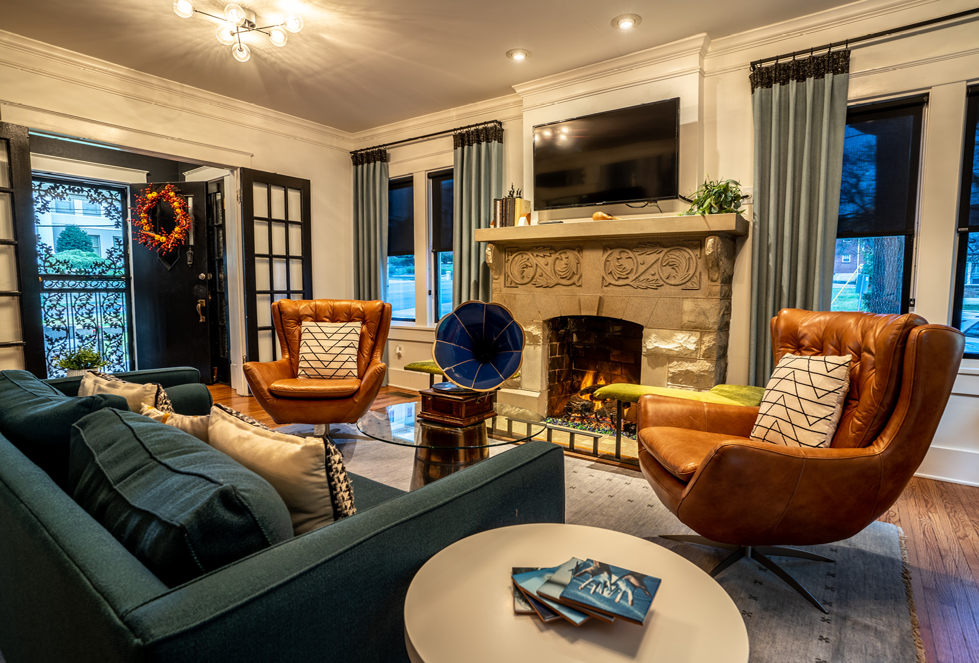 A couch, fireplace, and leather chairs in The NashVilla main room