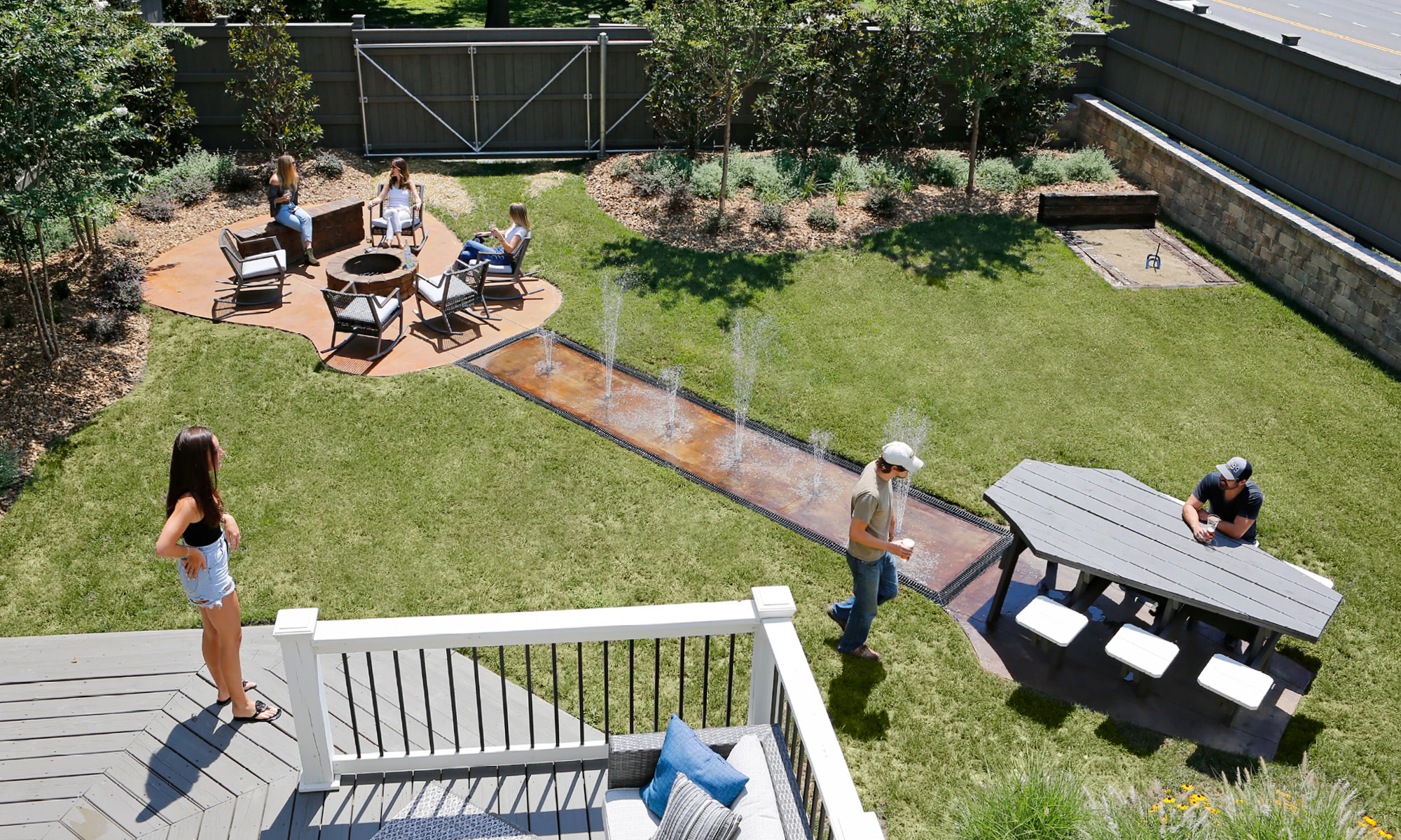 A beautiful backyard with a fire pit, water feature and picnic table that form the shape of a guitar